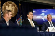 FILE - John Schoettler, Amazon vice president for real estate and facilities (L), joins New York Gov. Andrew Cuomo (C), and New York City Mayor Bill de Blasio during a news conference, Nov. 13, 2018, in New York. Amazon said it will split its much-an