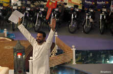"""Aamir Liaquat Hussain, host of the Geo TV channel program """"Amaan Ramazan"""", gestures while asking participants questions during a live show in Karachi, July 26, 2013."""