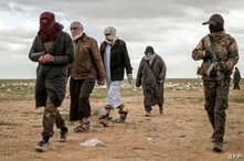 Men suspected of being an Islamic State (IS) group's fighter walk next to a member of the Kurdish-led Syrian Democratic Forces (SDF) as they wait to be searched after leaving the IS group's last holdout of Baghouz, Syria, Feb. 27, 2019.
