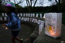 FILE - A volunteer helps setup lights in paper bags decorated with messages for the deceased during an Out of the Darkness Walk event organized by the Cincinnati Chapter of the American Foundation for Suicide Prevention in Sawyer Point park, Oct. 15,
