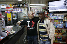 FILE - Robert, a migrant from Ghana, stands with his employer Massimiliano in a bar in Riace, Calabria region, Italy, Nov. 22, 2013.
