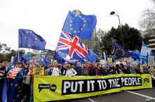 Demonstrators hold a banner during a Peoples Vote anti-Brexit march in London, March 23, 2019.