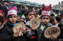 Palestinian children hold bread patties during a protest against aid cuts, outside the United Nations' offices in Khan Yunis in the southern Gaza Strip on January 28, 2018.