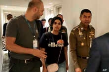 In this photo released by the Immigration Police, Chief of Immigration Police Maj. Gen. Surachate Hakparn, right, walks with Saudi woman Rahaf Mohammed Alqunun before leaving the Suvarnabhumi Airport in Bangkok, Thailand, Jan. 7, 2019.