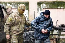 A Ukrainian sailor, right, is escorted by a Russian intelligence officer to a court room in Simferopol, Crimea, Nov. 27, 2018.