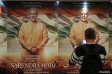 """A man uses his mobile phone to take photographs of a poster of the now delayed film """"PM Narendra Modi"""" in Mumbai, India, Jan. 7, 2019."""