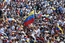 An opposition supporter waves a national flag during a gathering with Venezuelan opposition leader Juan Guaido, in Caracas on Feb. 2, 2019.