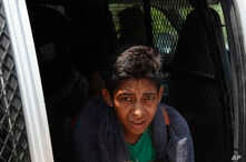A Central American migrant detained by Mexican immigration agents looks out from a van on the highway to Pijijiapan, Mexico, Monday, April 22, 2019.