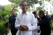 Incumbent Indonesian President Joko Widodo, center, smiles upon arriving for a meeting with leaders of his coalition parties in Jakarta, Indonesia, April 18, 2019.