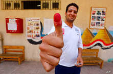 A man shows his ink-stained finger at a polling station, during the referendum on draft constitutional amendments, in Cairo, Apr. 20, 2019.