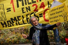 A woman holds a board that reads in French: 'One billion for Notre Dame! Zero for homeless' next to a banner that read also in French: 'One billion in 24 hours! Homeless Zero' during a protest in front of the Notre Dame cathedral in Paris, April 22, ...