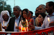 People hold candles to pay respects to the victims of Sri Lanka's serial bomb blasts, in Islamabad, Pakistan, April 24, 2019.