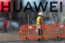 Workers clean the front of the new Huawei flagship store due to open soon in Madrid, Spain, May 22, 2019.