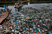FILE - A man guides a raft through a polluted canal littered with plastic bags and other garbage in Mumbai, India, Oct. 2, 2016.