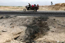 An Afghan family ride on a bike past the site of a car bomb attack where U.S. soldiers were killed near Bagram air base, Afghanistan,  April 9, 2019.