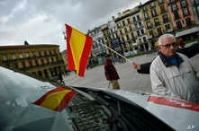A woman holds up a Spanish flag during an election rally to officially open the General Election campaign in Pamplona northern Spain, Thursday, April 11, 2019.
