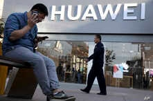 A man uses two smartphones at once outside a Huawei store in Beijing, May 20, 2019.
