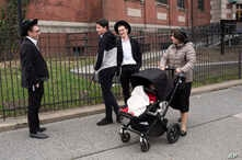A woman, right, who identified herself as Ester, passes a group of boys, April 9, 2019, in the Williamsburg section of Brooklyn, New York. Ester says that she does not believe that the measles vaccination is safe.