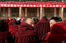 """About 90 monks sit in front of a red banner with white Tibetan and Chinese writing: """"Work Meeting for the Second Phase of Xicang Monastery's Rule of Law Propaganda Education Campaign,"""" ahead of the re-education study session at the 200 year old Xica..."""