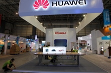 FILE - Workers prepare a stand for Huawei at the venue of the 21st Century Maritime Silk Road International Expo in Dongguan, Guangdong province, China, Oct. 28, 2015.