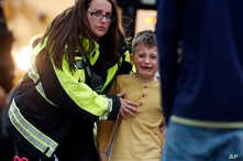 Officials guide students off a bus and into a recreation center where they were reunited with their parents after a shooting at a suburban Denver middle school in Highlands Ranch, Colorado, May 7, 2019.