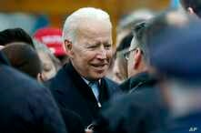 FILE - Former vice president Joe Biden talks with officials after speaking at a rally in support of striking Stop & Shop workers in Boston, April 18, 2019.