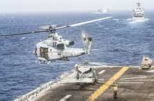 A UH-1Y Venom helicopter with Marine Medium Tiltrotor Squadron (VMM) 163 (Reinforced), 11th Marine Expeditionary Unit (MEU), takes off from the flight deck of the amphibious assault ship USS Boxer (LHD 4) during a strait transit.