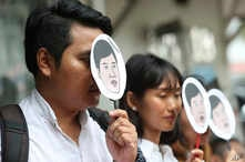 Demonstrators hold masks of Thai pro-democracy activist Sirawith Seritiwat during a protest at police headquarter in Bangkok, Thailand, July 3, 2019.