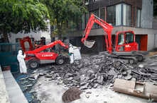 Workers direct a mechanical shovel grabbing pieces of destroyed surfacing to gather up the lead particles in the school yard of Saint Benoit primary school in Paris, France, Aug. 8, 2019.