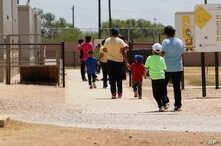 Immigrants seeking asylum leave a cafeteria at the ICE South Texas Family Residential Center, Aug. 23, 2019, in Dilley, Texas.