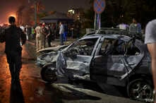 Police guard the wreckage of a car in front of the National Cancer Institute in Cairo, Egypt, after an explosion that happened when a vehicle drove the wrong way and hit several other cars. (H. Elrasam for VOA)