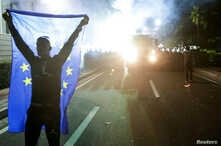 An opposition supporter holds an EU flag outside the Parliament building during an anti-government protest, calling on Prime Minister Edi Rama to step down, in Tirana, Albania, June 8, 2019.