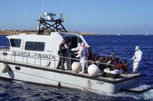 Migrants are evacuated by Italian Coast guards from the Open Arms Spanish humanitarian boat at the coasts of the Sicilian island of Lampedusa, southern Italy, Aug. 17, 2019.