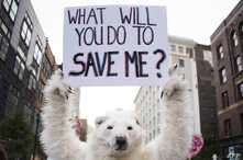 FILE - A anti-global warming protester holds up a sign in Cleveland, Ohio, near the Republican National Convention, July 18, 2016.