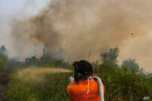 Firefighters spray water to extinguish brush fires in Kampar, Riau province, Indonesia, Sept. 11, 2019.