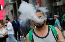 A man uses a vape as he walks on Broadway in New York City, September 9, 2019.