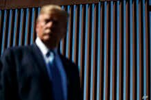With a section of the wall in the background President Donald Trump tours a section of the southern border wall, Wednesday,…