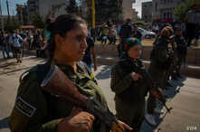 Kurdish soldiers stand guard at a rally in support of the Kurdish forces, in Qameshli, Syria, Oct. 23, 2019. (Yan Boechat/VOA)