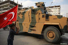 A boy waves a Turkish flag as Turkish military vehicles drive on a street in the Turkish border town of Akcakale in Sanliurfa…
