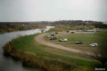 U.S. border patrol cars are seen through the fence of the bridge connecting Eagle Pass, Texas, with Piedras Negras, Mexico,…
