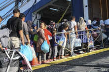 Refugees and migrants board a ferry on the island of Lesbos to be transferred to the port of Piraeus on October 6, 2019.