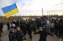 FILE - Ukrainian army veterans and volunteers wave the national flag at a checkpoint near the town of Zolote, Luhansk region, Ukraine, Oct. 9, 2019.