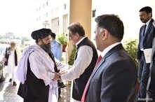 Pakistan's Foreign Minister Shah Mehmood Qureshi welcomes Mullah Abdul Ghani Baradar, who a leading Taliban delegation, upon his arrival at the Ministry of Foreign Affairs, in Islamabad, Pakistan, Oct. 3, 2019.