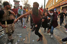 Iraqi anti-government protesters carry away an injured comrade amidst clashes with security forces by the capital Baghdad's…