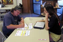 FILE - Molly McGrath, who works for VoteRiders to help people get the required photo identification needed to vote, helps Matthew Kurtz fill out a voter registration form in Madison, Wisconsin, Aug., 31, 2016.