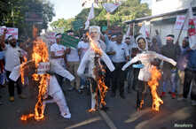 Activists burn effigies depicting India's Home Minister Amit Shah, Prime Minister Narendra Modi and Chief Minister of Assam Sarbananda Sonowal, during a protest against the Citizenship Amendment Bill, in Guwahati, India, Dec. 4, 2019.