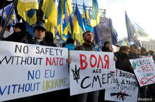 """People take part in a rally in Kyiv, Ukraine, Dec. 8, 2019, ahead of the so-called """"Normandy"""" format summit in Paris, where leaders of Ukraine, Russia, Germany and France will meet to discuss steps to resolve the conflict in eastern Ukraine."""