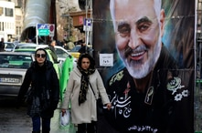 Women walk past a banner of Iranian Revolutionary Guard Gen. Qassem Soleimani, who was killed in Iraq in a U.S. drone attack on…