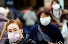 Pedestrians wear protective masks as they walk through a shopping district in Tokyo, Jan. 16, 2020.
