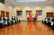In this photo released by Office of the Commander in Chief of Defense Services, Myanmar's Army Commander Senior Gen. Min Aung Hlaing, center left, speaks with Chinese President Xi Jinping, center right, at a hotel in Naypyitaw, Myanmar, Jan. 18, 2020.
